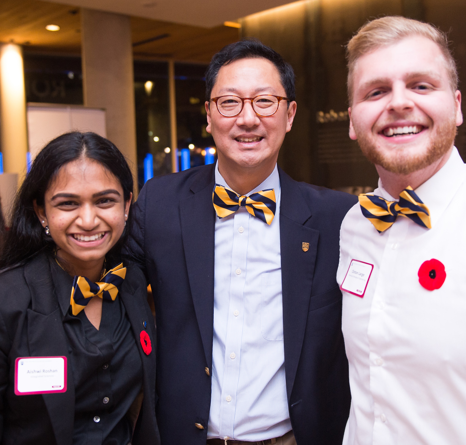 UBC President Santa J. Ono with two UBC students, wearing blue and gold bowties, at the Donor Night Nov 9, 2016