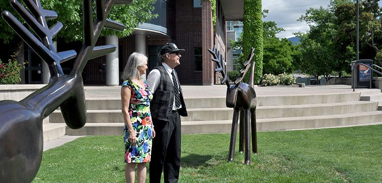 "Louise Sidley, left, and David Sidley speak to family and friends gathered after the sculpture ""Pair of Deer"" was officially unveiled at UBC's Okanagan campus."